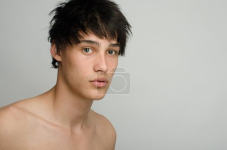 Portrait of an innocent handsome topless man posing fashion. Young guy with cool messy hairstyle