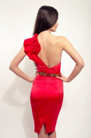 Girl posing fashion in sexy red dress with naked back and tight on the butt. Beautiful brunette woman wearing a one sleeve red dress and holding her hand on her waist