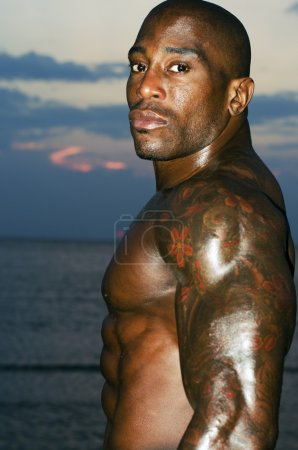 Black bodybuilder topless. Strong man with perfect abs, shoulders,biceps, triceps and chest posing at sunrise