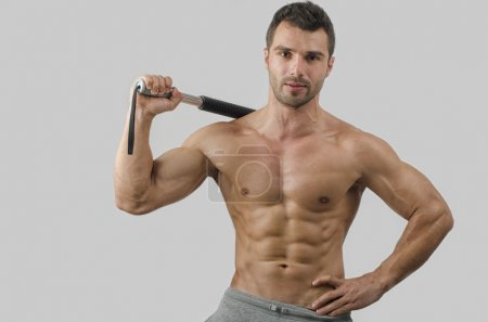 Bodybuilder training with a bendy bar. Strong man with perfect abs, pecs shoulders,biceps, triceps