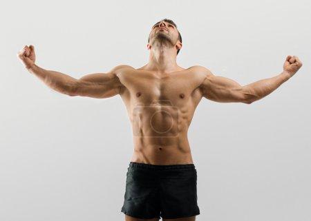 Photo pour Culturiste fort homme avec abdos parfaits, épaules, biceps, triceps et poitrine fléchissant ses muscles - image libre de droit