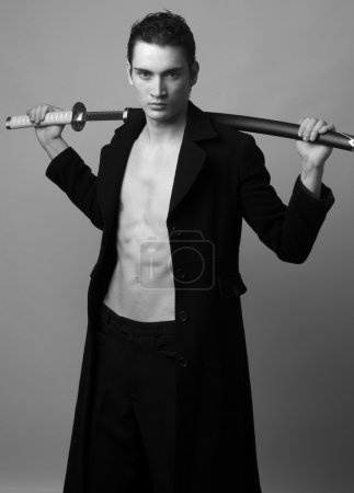 Man dressed in a long black coat with six pack abs...