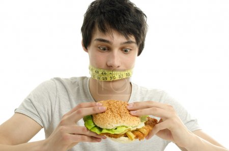Man with a centimeter on his mouth unable to eat a big hamburger, young man dieting and having a hard time with fast food