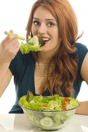 Happy woman eating organic salad. Woman keeping a diet with green salad. Close up on a young woman eyes holding a bowl of organic salad, eating healthy