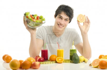 Happy man having a table full of organic food,juices and smoothie. Cheerful young man eating healthy salad and fruits. Isolated on white