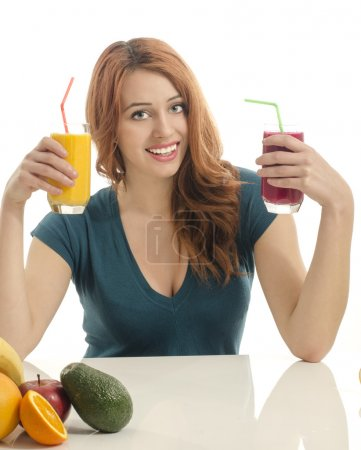 Happy woman holding two different organinc smoothie. Cheerful young woman eating healthy fruits  and drinking orange juice and green smoothie.
