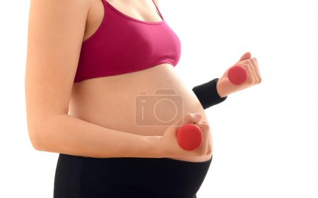 Close up on pregnant belly. Woman expecting a baby training with pink dumbbell