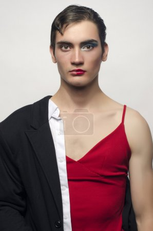 Half man, half woman, wearing a black suit and a red dress.Angry man wearing make up, Portrait of a drag queen.