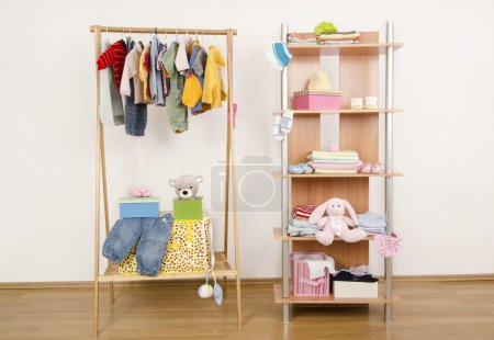 Dressing closet with clothes arranged on hangers.Wardrobe of newborn,kids, babies full of all shades of blue an orange clothes, shoes,accessories and toys