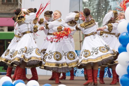Girls in traditional costumes dancing on stage