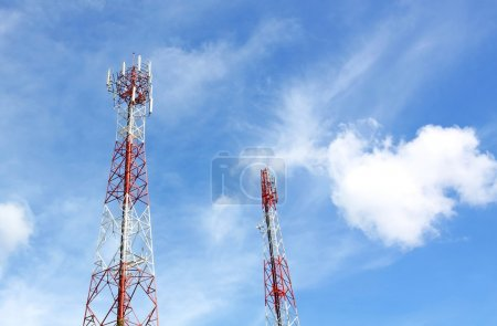 Cell phone and communication towers against blue sky with scatte