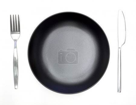 Knife, black plate and fork isolated on white background