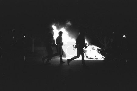 Photo pour LAPD officiers en tenue anti-émeute gear course passé brûlant voiture radio de police durant les émeutes de rois de rodney à los angeles, 29 avril 1992 - image libre de droit