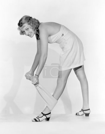 Woman stretching with a towel wrapped around her leg