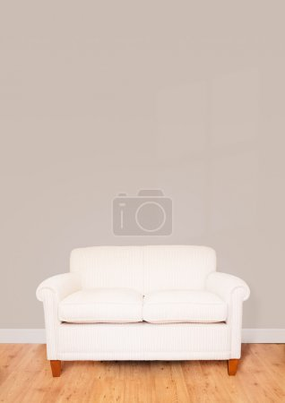 Photo for Modern cream sofa against a blank wall with lots of space for text - Royalty Free Image