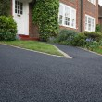 New bitumen driveway outside a beautiful brick hou...