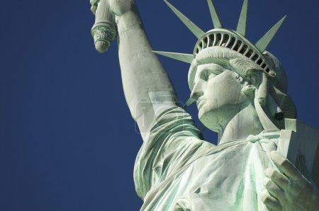 Photo pour Statue de la Liberté profil rapproché avec couronne et livre contre ciel bleu - image libre de droit
