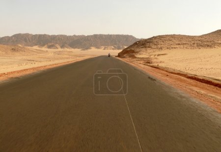 Africa. The road running through the Sahara desert. Unknown man riding a motorcycle on the road.