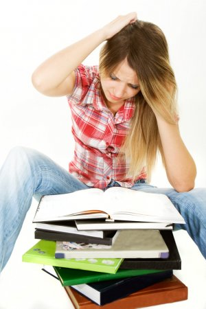 puzzled student girl with pile of books over white