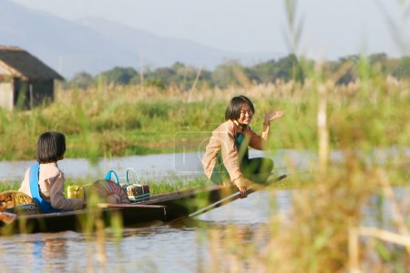 two young girls in wooden canoe
