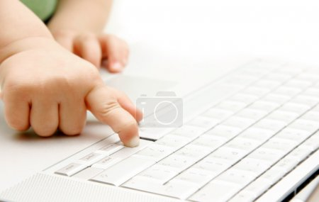 close up of child finger pressing key on laptop keyboard