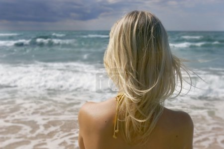 Girl looking into stormy sea