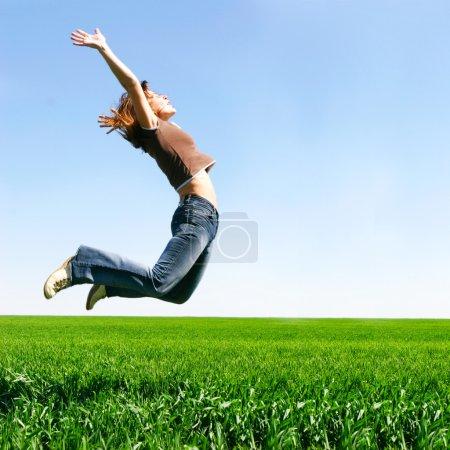 Photo pour Fille heureuse sautant sur fond naturel - image libre de droit