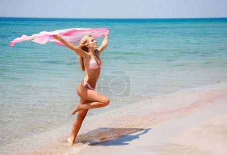 Photo pour Jeune fille heureuse sautant sur la plage - image libre de droit
