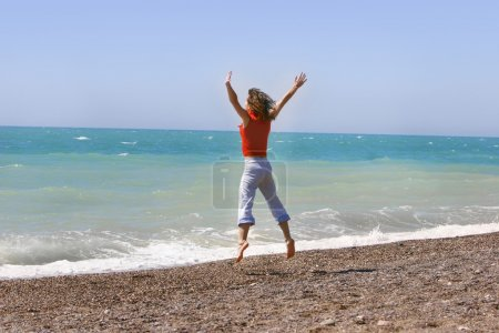 Young woman jumping happily on the beach
