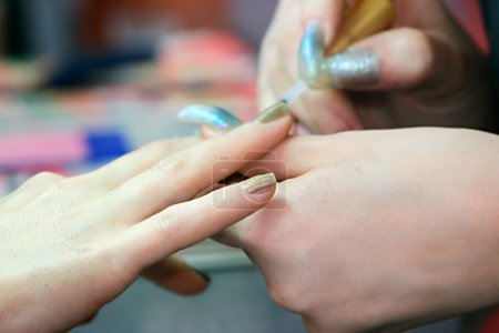 manicuring fingernails in beauty salon