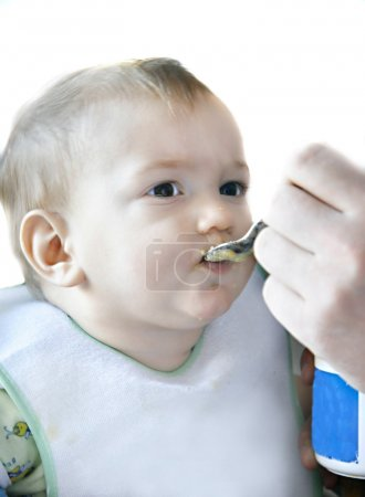 Eating baby boy over white, focus on eyes