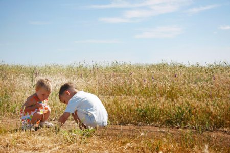 Two kids playing on rural background