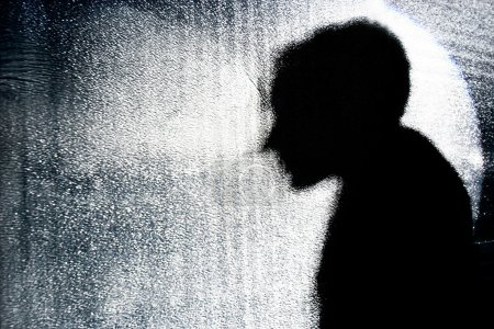 person's silhouette behind textured glass wall