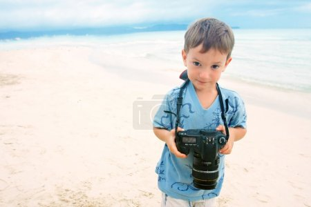 Photo for Young boy with photo camera on beach background - Royalty Free Image