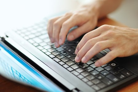 Photo pour Mains d'homme taper sur un clavier d'ordinateur portable noir - image libre de droit