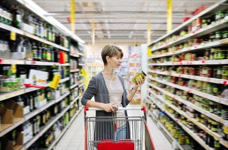 Photo pour Jolie femme avec un panier shopping et le choix des marchandises au supermarché - image libre de droit