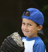 Hispanic baseball boy with blue and white clothes and glove on d