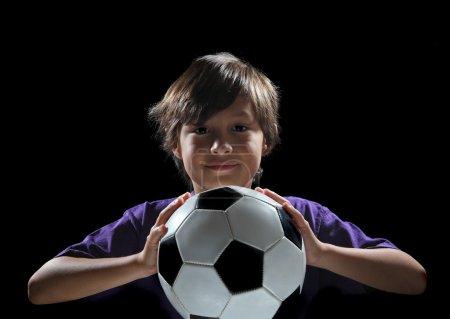 Boy with soccer ball on dark background