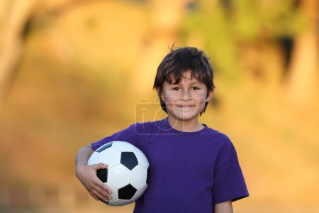 Boy with soccer ball at sunset