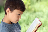 Young boy reading book outside