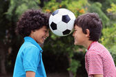 Two young boys playng with a soccer ball