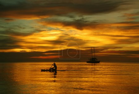 Sailing boat on the sea, a man on a beautiful golden sunset