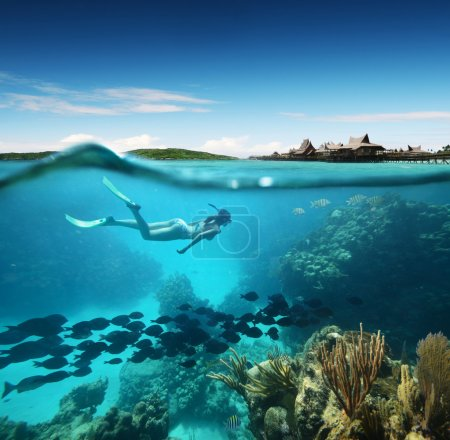 Young woman snorkeling in the coral reef in the tropical sea against the backdrop of the islands