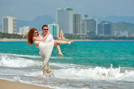 Romantic happy couple on the beach on a background of the spa to