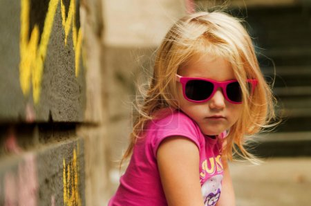 Modern girl sitting in pink glasses near a wall