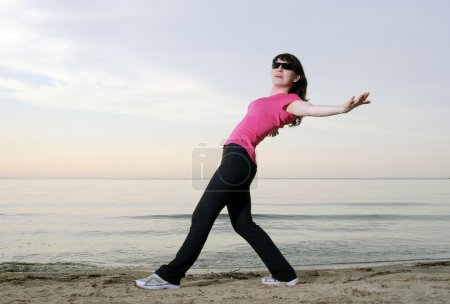 Woman Exercising on the beach in sunglasses
