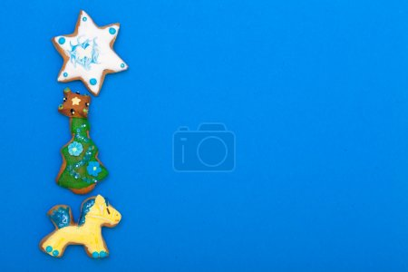 Gingerbread cake pony christmas tree star with icing decoration on blue