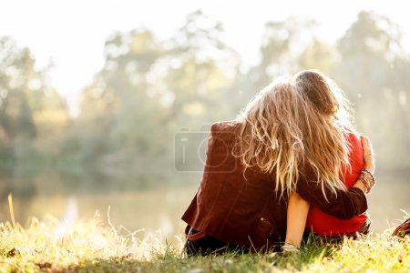 Two young women sitting on grass hugging rear view...