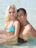 Portrét mladý hezký pár dobře baví na pláži