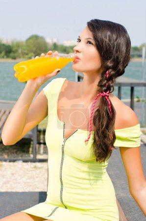 Photo pour Belle brunette fille moderne, rafraîchissante avec jus d'orange par une chaude journée d'été. à l'extérieur. - image libre de droit